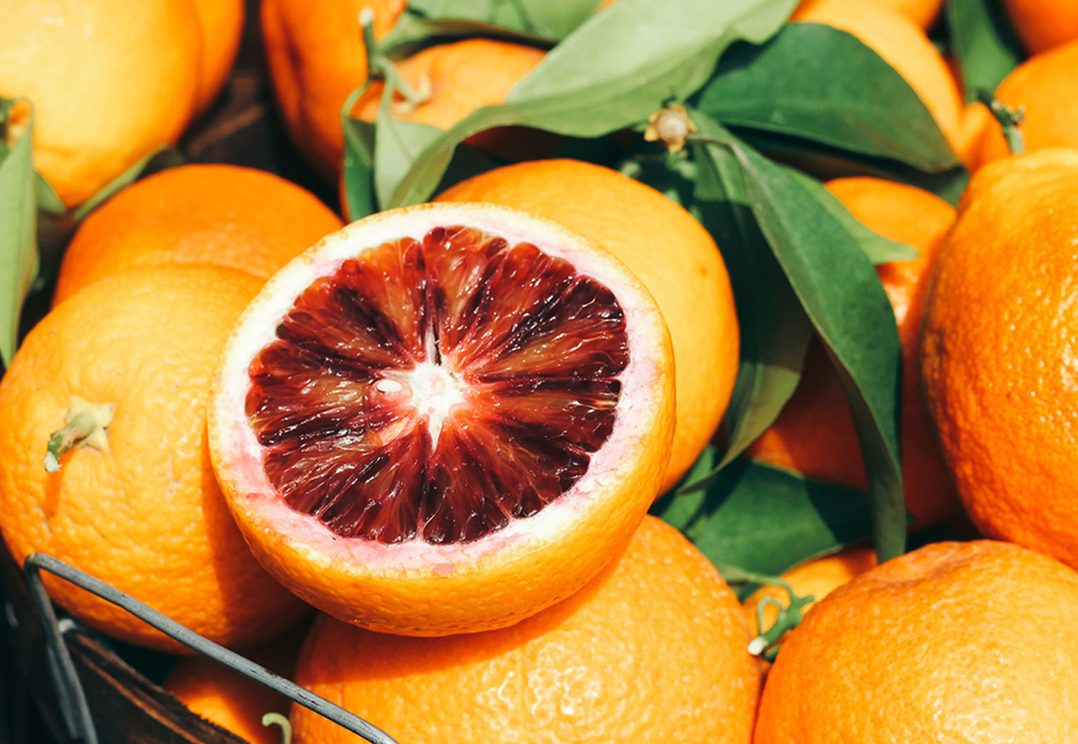 Basket of Sicillian Blood Oranges, with one cut open to see the ruby-red flesh