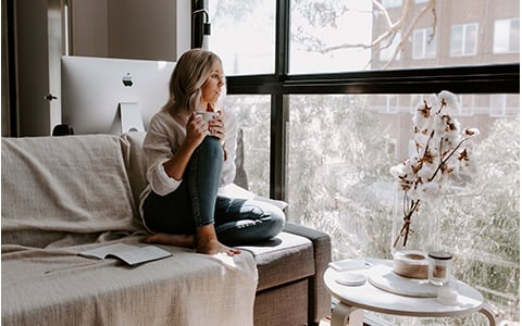 Woman sitting on couch looking out window and drinking tea