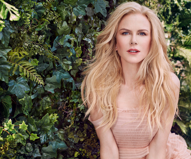 Nicole Kidman standing in front of green shrub